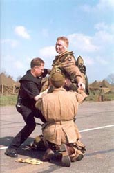 Major Robert L. Strayer (actor Phil McKee) being helped into his parachute harness.