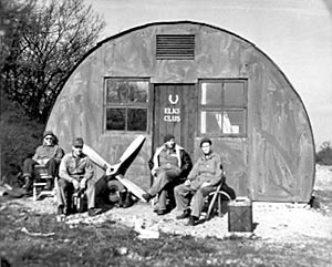 Nissen hut near the perimeter track. The propellers and tyre are from Piper L-4 Cubs. The man on the extreme right of the picture is Robert A. Stone who kindly supplied the photograph